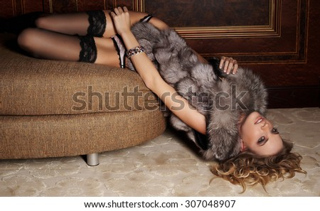Sexy slim female with golden hair and fur coat lying on the floor in antique apartment. - stock photo