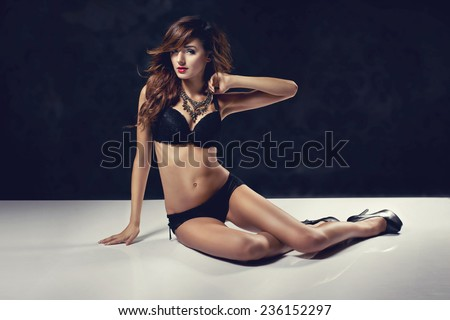 Sexy slim woman posing in black lingerie. Sensual pose  - stock photo