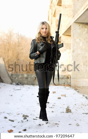 Sexy smiling girl holding a weapon outdoors - stock photo
