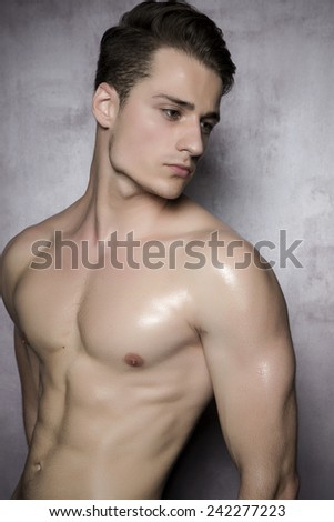 Sexy smiling shirtless male model flirting against of grunge wall. - stock photo