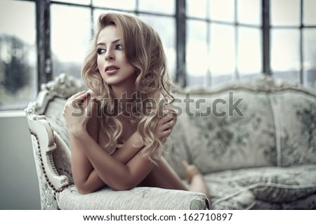 Sexy smiling woman relaxing in bed covering her breast.  - stock photo