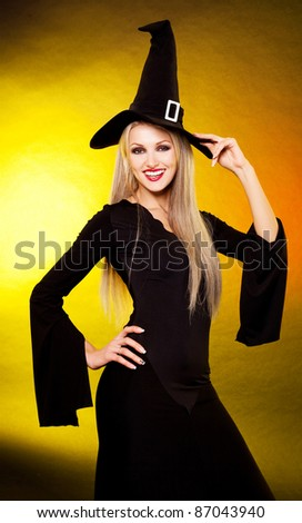 sexy smiling young blond witch, against yellow background - stock photo