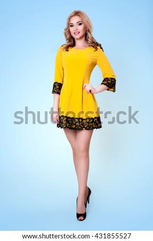 Sexy stunning blonde posing on yellow dress on blue - stock photo