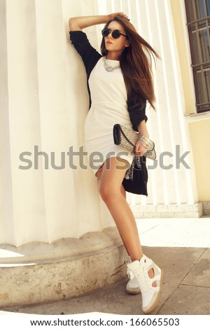 sexy stylish girl in white dress and gumshoes standing outdoors - stock photo