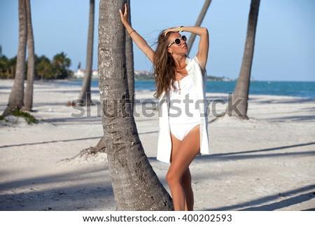 Sexy suntan woman relaxing enjoying sunset on exotic beach. Lady sunbathing during summer holiday. - stock photo