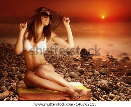 Sexy tanned model posing on the beach on red dramatic sunset background, stony coastline, fog over sea, seduction and beauty concept, summer vacation - stock photo