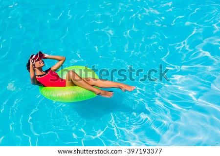 Sexy tanned    woman in red swimsuit having fun and enjoying  summer in amazing big swimming pool. Young pretty girl  swimming on inflatable ring.  Stylish transparent cap. Beach party. - stock photo