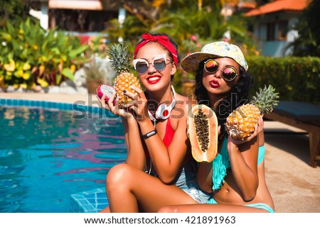 Sexy teen girls tanning,wearing Glamor sunglasses Eating fresh fruits outdoor.Sensual Lips.Hipster Girls,pineapple.Bright Manicure and Lipstick.Desire.Beauty friends,happy mood,party girls,gossip girl - stock photo