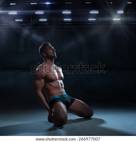 Sexy Thoughtful Athletic Man in Boxer Brief Only Kneeling on the Floor Inside a Building While Looking Up. - stock photo