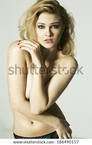 sexy topless woman in panties with arm covering breasts, studio shot - stock photo