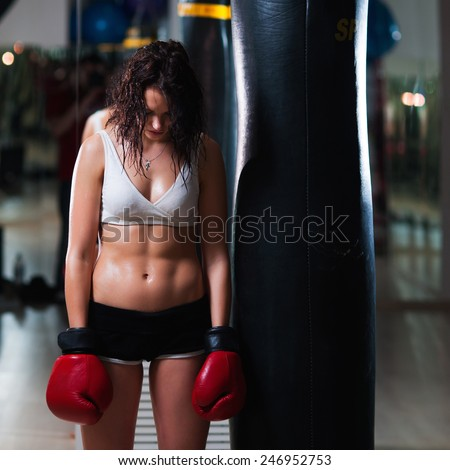 Sexy upset brunette female boxer standing by the punching bag - stock photo