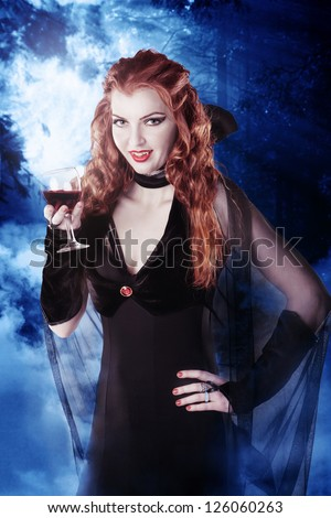 Sexy vampire girl with glass of blood in the woods at night - stock photo