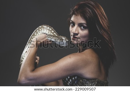 Sexy warrior tattooed woman with big snake and iron corset - stock photo