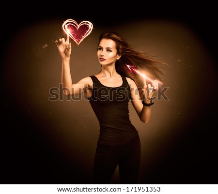 Sexy Woman Aiming to the Glowing Heart with an Arrow on Dark Background. Fantasy Cupid Concept for Valentine's Day. - stock photo
