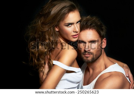Sexy woman and man in intimacy relations - fashionable couple posing at studio - stock photo