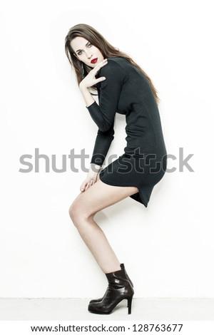 Sexy woman at white wall posing - stock photo