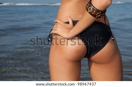 sexy woman back with black lingerie on seashore - stock photo