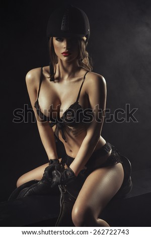 Sexy woman body with saddle and helmet like jockey  - stock photo