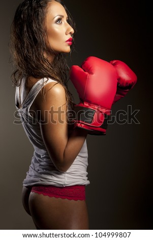 Sexy woman boxer with her hair damp from perpiration pausing during training showing her cute bum - stock photo