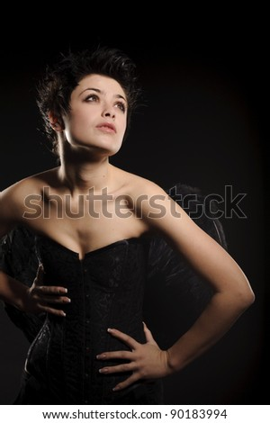 Sexy woman brunette woman in corset, isolated on black - stock photo
