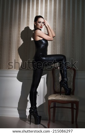 Sexy woman dancer in latex catsuit step on chair - stock photo