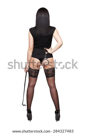 Sexy woman dominatrix in stockings holding whip and handcuffs, sex toys for bdsm, isolated on white. Back view - stock photo