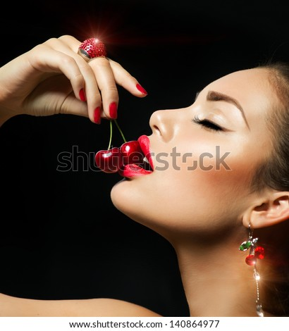Sexy Woman Eating Cherry. Sensual Red Lips. Red Manicure, Lipstick and Ring. Desire. Sexy red Lips with Cherries isolated on Black - stock photo