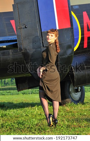 sexy woman in an army dress standing next to a WWII bomber - stock photo