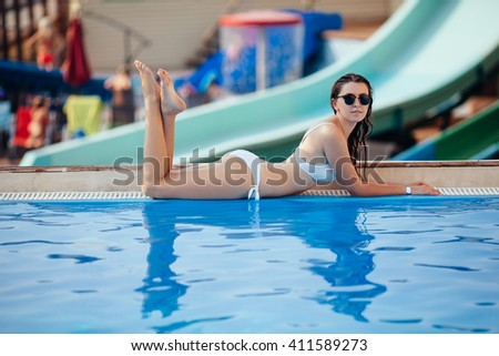 Sexy woman in bikini enjoying summer sun and tanning during holidays near pool. Top view. Woman in swimming pool. Sexy woman in bikini. - stock photo