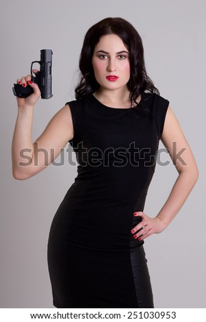 sexy woman in black dress holding gun over grey background - stock photo
