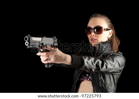 Sexy woman in black holding a revolver - stock photo