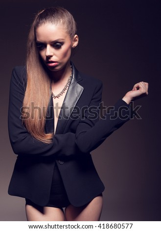 Sexy woman in black lingerie covering her body with black blazer - stock photo