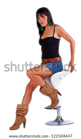 Sexy woman in blue jean skirt sitting on a stool while isolated on white. - stock photo