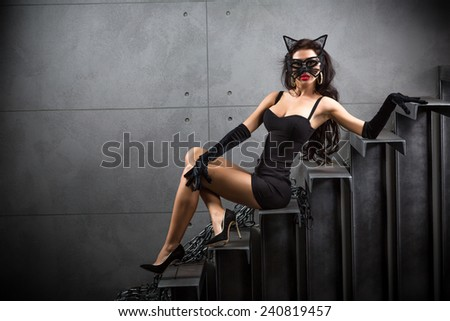 sexy woman in cat woman suit lying on stairs at backyard of building - stock photo