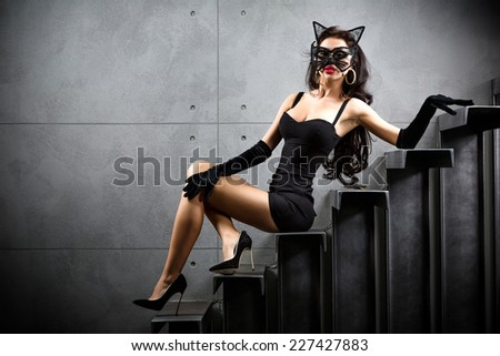 sexy woman in catwoman suit lying on stairs at backyard of building - stock photo