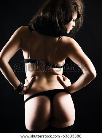 Sexy woman in erotic lingerie over dark background - stock photo