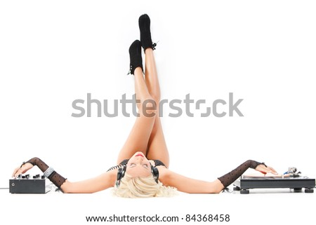 sexy woman in headphones lying with dj equipment and her legs on the white wall - stock photo