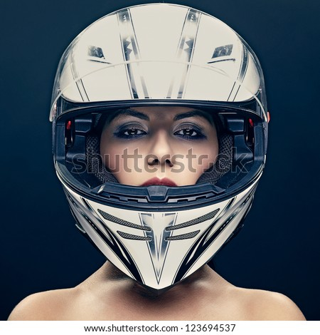 Sexy woman in helmet on dark background - stock photo
