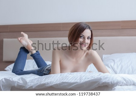 sexy woman in jeans posing topless on bed - stock photo