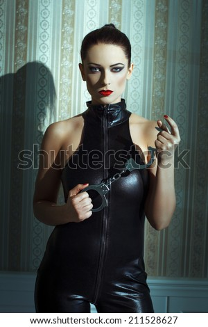 Sexy woman in latex catsuit and handcuffs posing at vintage wall - stock photo