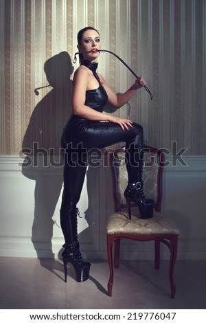 Sexy woman in latex catsuit bite whip at vintage wall - stock photo