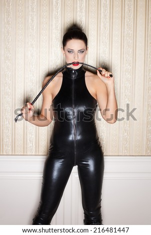 Sexy woman in latex catsuit bite whip, bdsm - stock photo