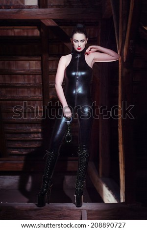 Sexy woman in latex catsuit posing on timber at night with handcuffs, bdsm - stock photo