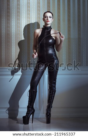 Sexy woman in latex catsuit with whip posing at vintage wall - stock photo
