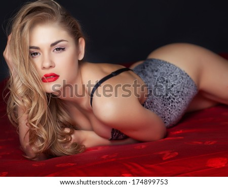 Sexy woman in lingerie lying on the bed - stock photo