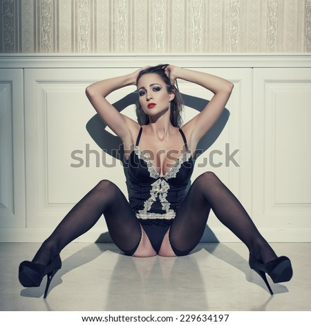 Sexy woman in lingerie sit on floor at night, vintage style - stock photo