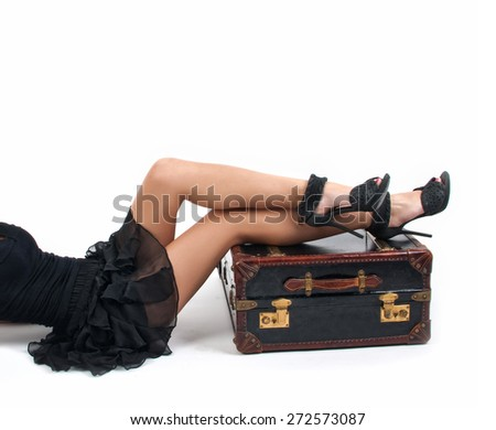 Sexy woman in little black dress keeping the legs on a vintage suitcase, isolated on white background, studio shot. Side view of perfect body female with long beautiful legs on high heels - stock photo