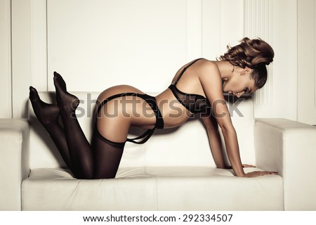 sexy woman in seductive black lingerie sitting on a couch in stockings - stock photo