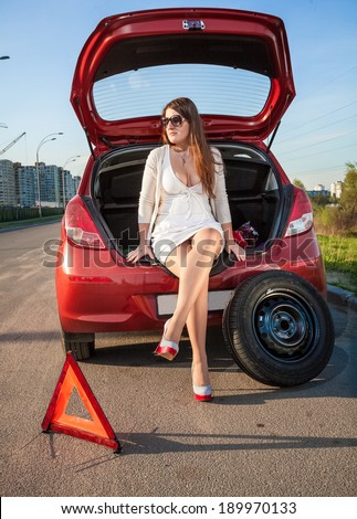 Sexy woman in short dress waiting for help near broken car - stock photo