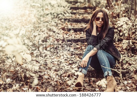 Sexy woman in sunglasses posing in a park - stock photo